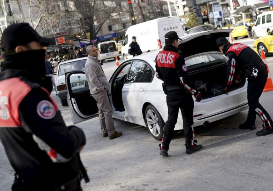 Police officers search a car during a security control check in central Ankara, Turkey March 17.