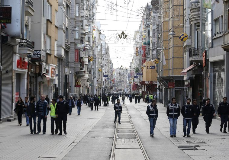 Plain clothes police walk on the main pedestrian street of Istiklal in central Istanbul during a May