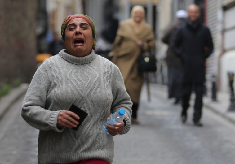 A woman flees the scene of the suicide bombing in Istanbul