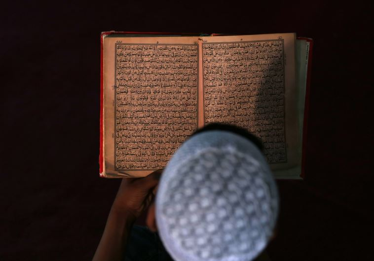 An Afghan boy reads the Koran in a madrasa, or religious school, during the Muslim holy month of Ram