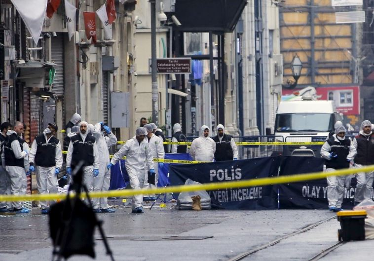Police forensic experts inspect the area after a suicide bombing in Istanbul