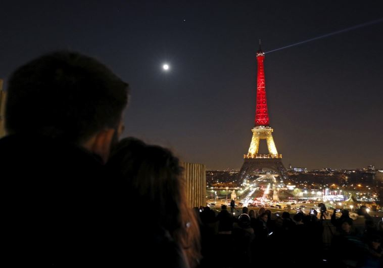 A couple looks at the Eiffel Tower lit up in the colors of the Belgian flag in Paris