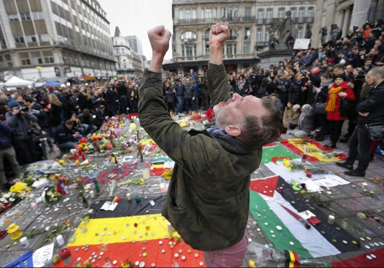 A man reacts at a street memorial following Tuesday's bomb attacks in Brussels