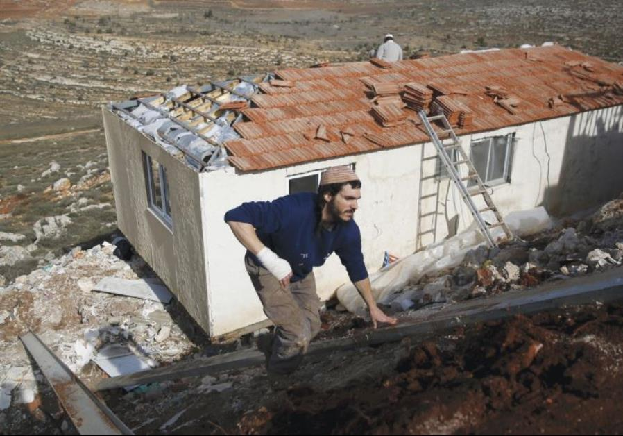 SETTLERS WORK on the construction of a house in the outpost of Achia in the Binyamin region