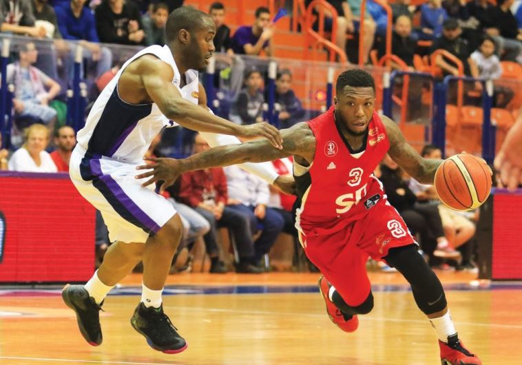 Hapoel Tel Aviv guard Nate Robinson (right) drives past Ironi Nahariya's Michael Umeh (left)