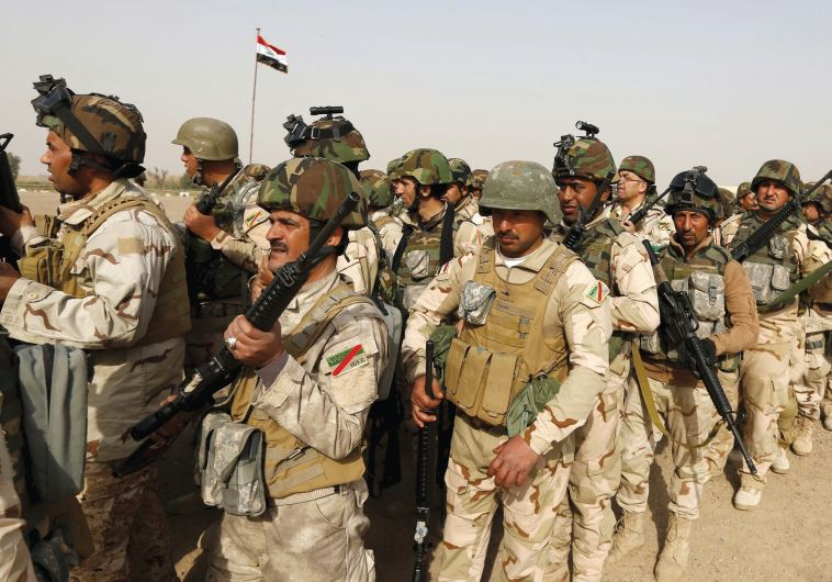 IRAQI SECURITY forces wait for vehicles traveling to Mosul to fight against Islamic State at an Iraq
