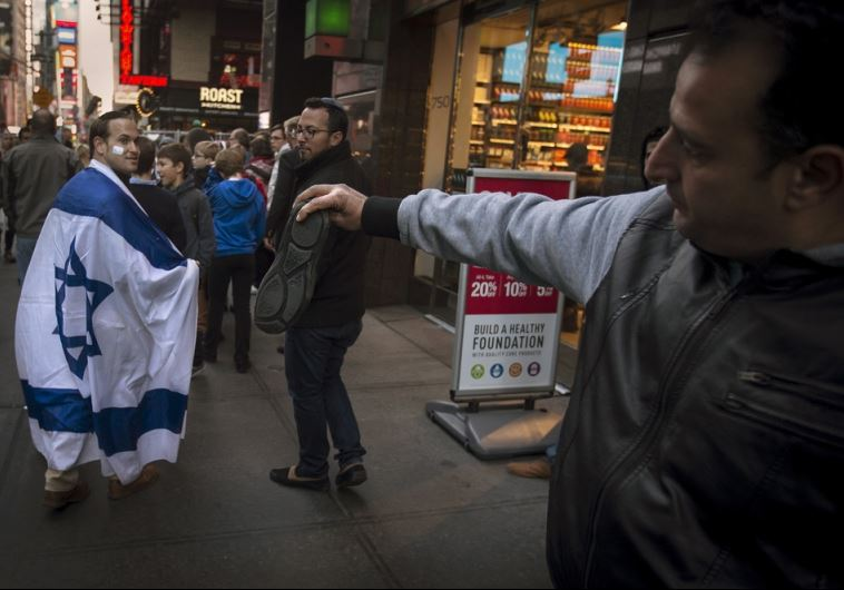 A man, draped in an Israeli flag, reacts while walking past a pro-Palestinian demonstrator