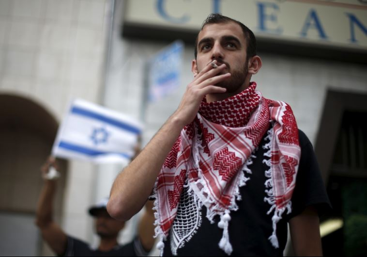 A Palestinian protester stands next to an Israeli counter-protest during a demonstration in LA