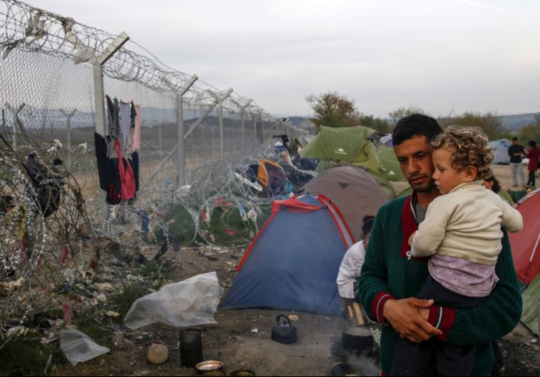 A man with a child looks at the border fence at a makeshift camp for migrants and refugees