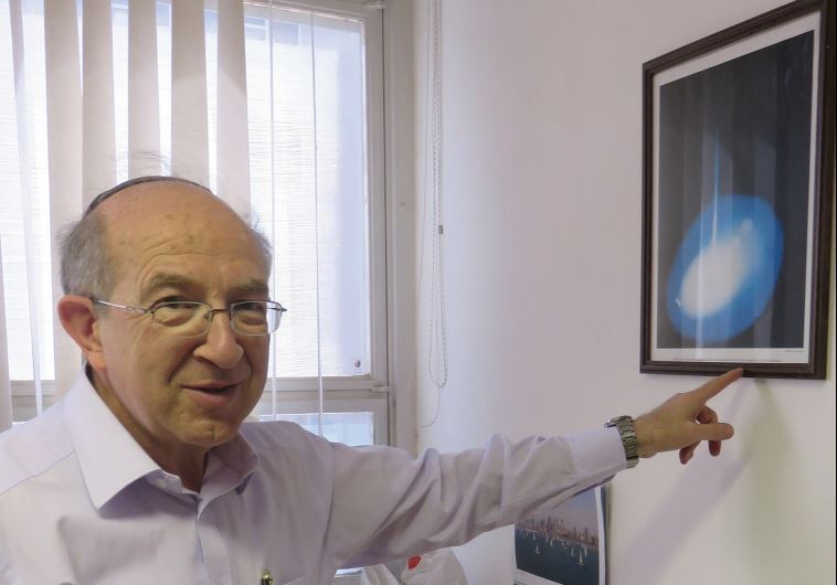 DR. YEHEZKEL CAINE points to a Gemini mission photo given to him by NASA.