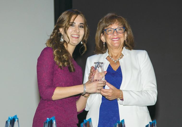 ALLISON JOSEPHS (left) presents an award to Baroness Ros Altmann, Britain's pensions minister.
