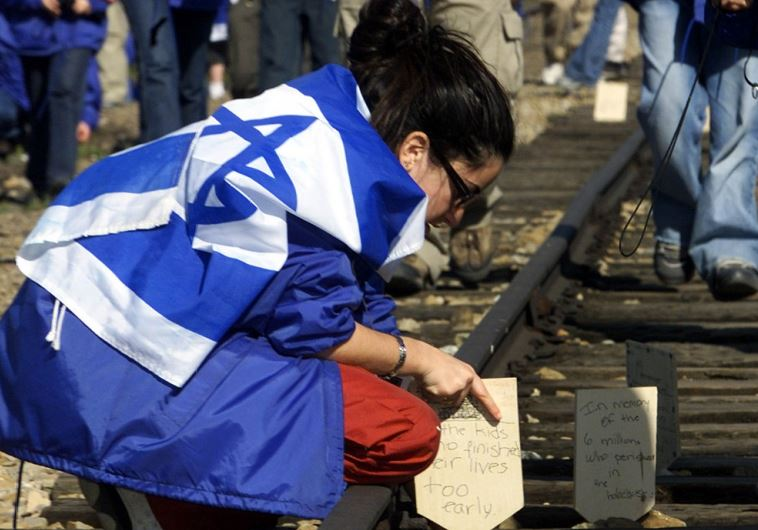 A Jewish girl places a wooden board on railway tracks to commemorate her killed relatives