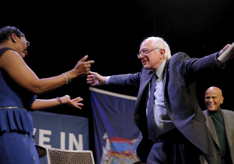 US Democratic presidential candidate and US Senator Bernie Sanders hugs former Ohio State Senator Ni