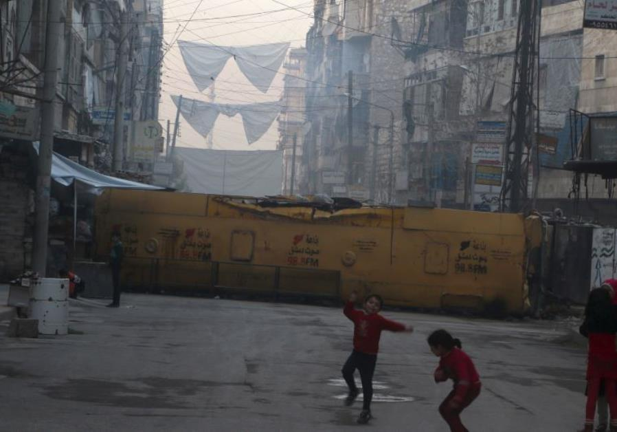 Children play near a bus barricading a street, which serves as protection from snipers loyal to Syri