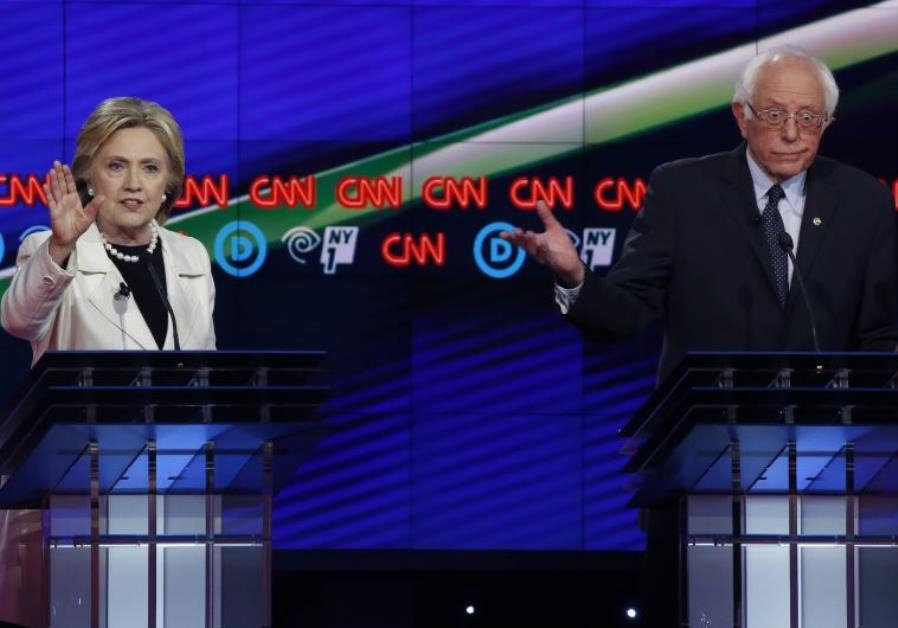 Democratic U.S. presidential candidate Hillary Clinton (L) speaks as Senator Bernie Sanders reacts d