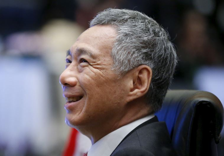 Singapore's Prime Minister Lee Hsien Loong talks with government officials during the Plenary sessio