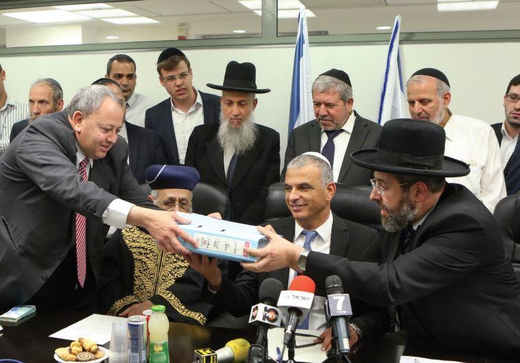ASHKENAZI CHIEF RABBI David Lau hands a box containing the symbolic hametz (leavening).