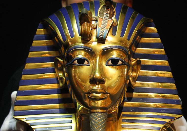 A worker shows to media a replica of a golden death mask of Pharaoh Tutankhamun