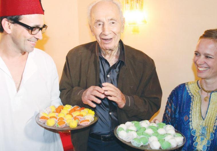 FORMER PRESIDENT Shimon Peres enjoys a post-Passover sweet at a Mimouna celebration in Tel Aviv.
