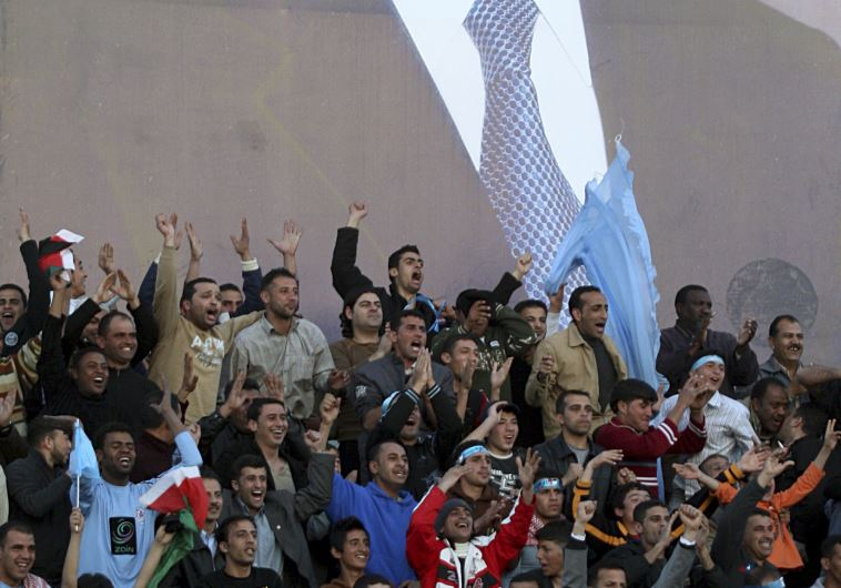 Fans cheer Jordan's Al-Faysali team during a soccer match against Morocco's Al Raja during their Ara