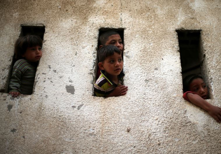 Palestinian boys look out of their house in Beit Lahiya town in the northern Gaza Strip