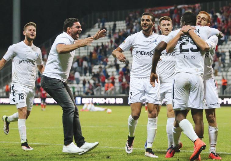 Ironi Kiryat Shmona coach Shlomi Dora (second left) celebrates with his players after Austin Amutu s