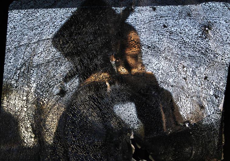 An ultra-Orthodox Jewish man is seen through a damaged car window