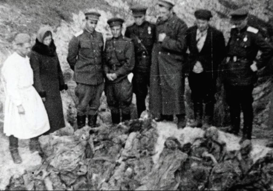 SOVIET SOLDIERS stand by a mass grave in Lyady, Belarus, in 1943.