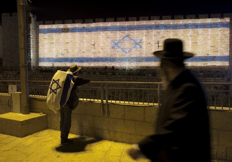 A man with an Israeli flag covering his backpack looks at an Israeli flag made of lights