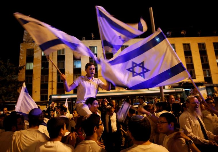Israelis dance with Israeli national flags during celebrations marking Israel's Independence Day