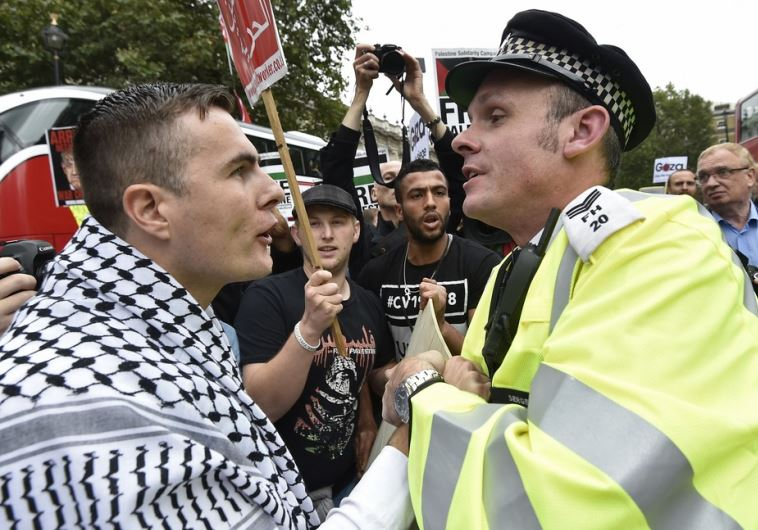 A pro-Palestinian demonstrator argues with police during a protest outside Downing Street in London