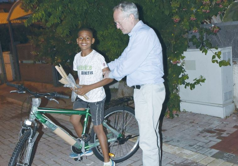 ONEFAMILY founder and chairman Marc Belzberg presents a bicycle yesterday.