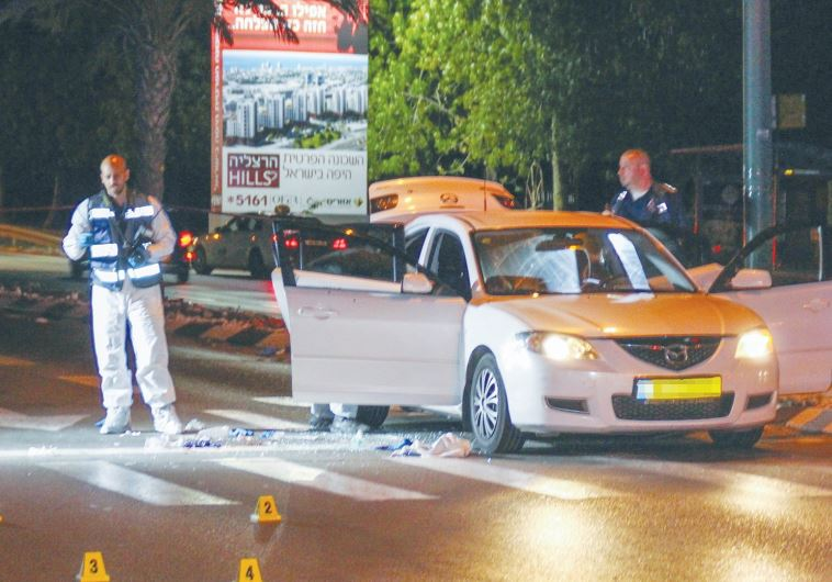 A FORENSICS OFFICER examines the car in Tel Aviv in which mob prince Shay Shirazi was shot to death.