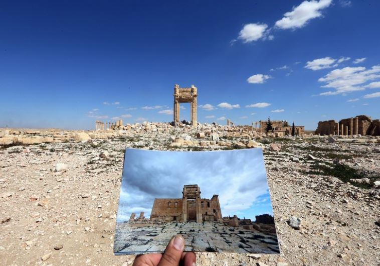 A general view taken on March 31, 2016 shows a photographer holding picture of the Temple of Bel