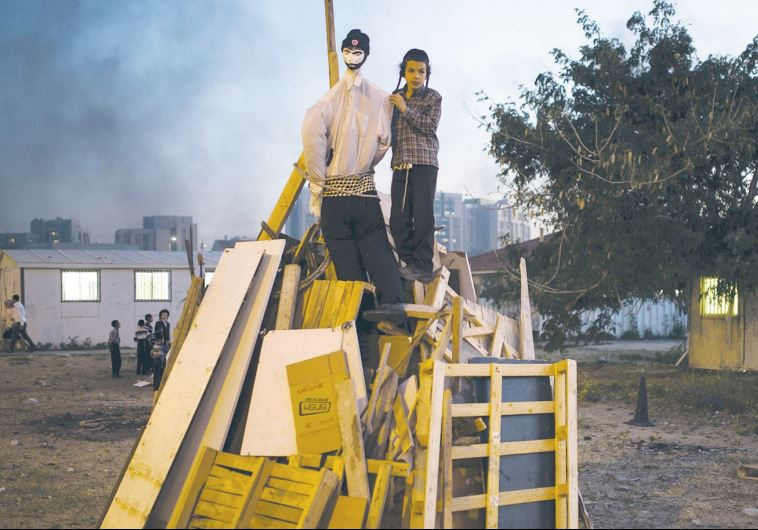 AN ULTRA-ORTHODOX BOY stands atop a pile of wood prepared for a Lag Ba'omer bonfire in Ashdod
