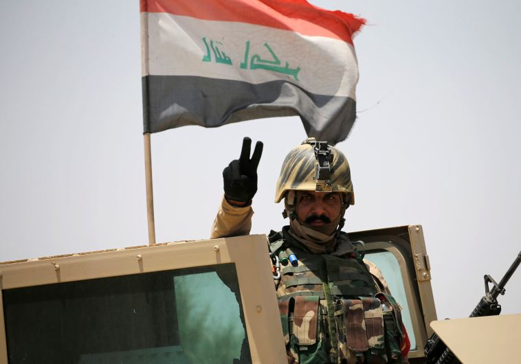 An Iraq soldier gestures near Falluja, Iraq