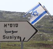 A road sign in English, Hebrew, and Arabic points to the Israeli settlement of Susiya