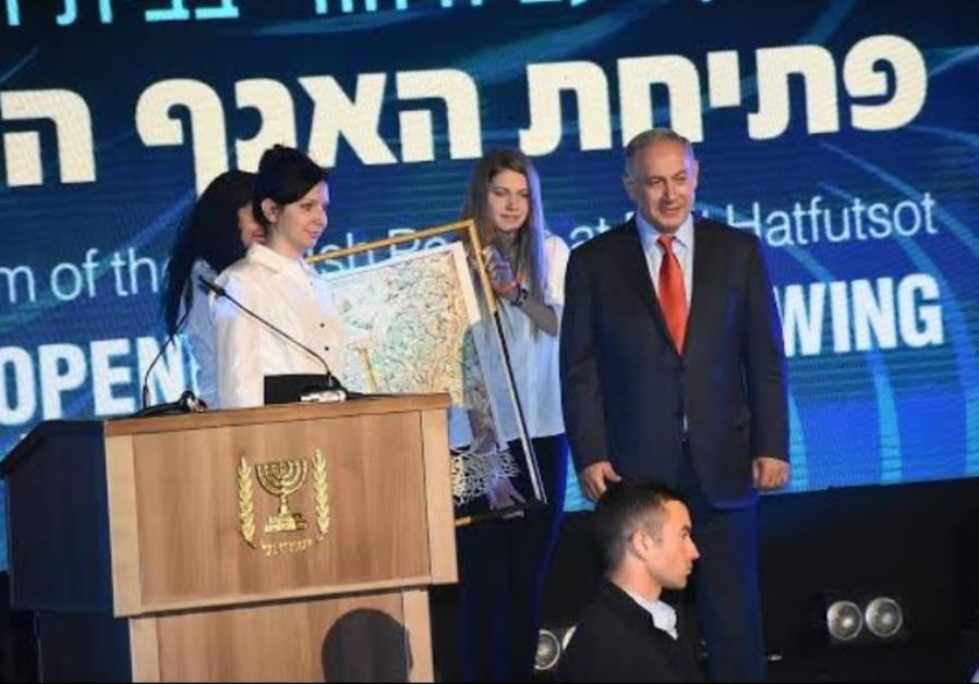Irina Nevzlin, chair of Beit Hatfutsot board of directors, presents family tree to Netanyahu