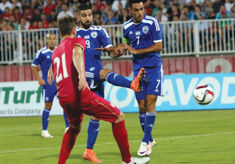 Israel striker Munas Dabbur (center) attempts a shot