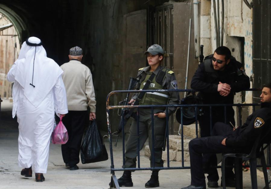 A SPLIT CITY: Two Arab men walk past police officers in the Old City of Jerusalem