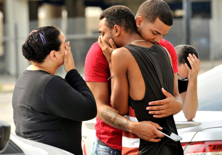 Friends and family members embrace outside the Orlando Police Headquarters during the investigation