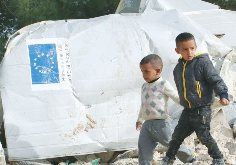 PALESTINIAN BOYS walk past the remains of their family's home in the West Bank