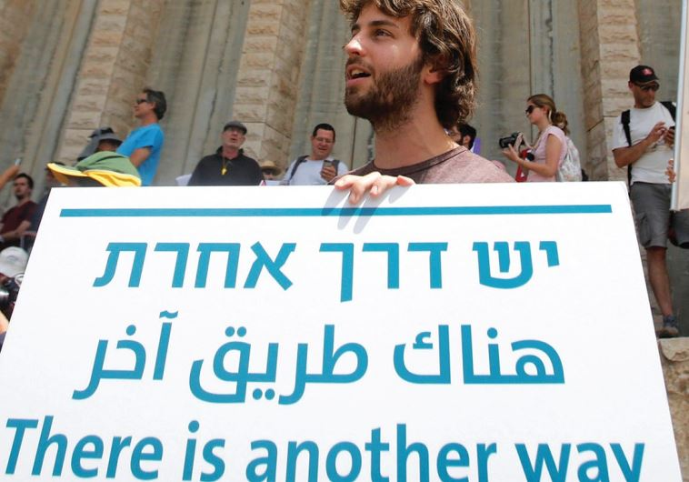 A DEMONSTRATOR holds a sign during a demonstration by Palestinian and Israeli activists