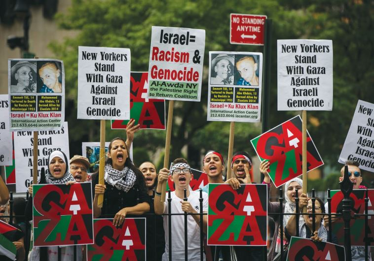 PRO-PALESTINIAN DEMONSTRATORS display signs outside New York's City Hall in July 2014, near where a