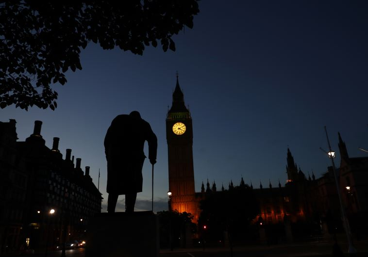 Dawn breaks behind the Houses of Parliament and the statue of Winston Churchill in Westminster, Lond
