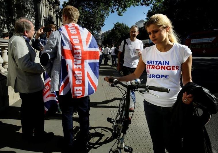 A vote remain supporter walks past a vote leave supporter outside Downing Street after Britain voted
