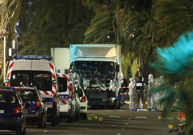 French police forces and forensic officers stand next to a truck July 15, 2016 that ran into a crowd
