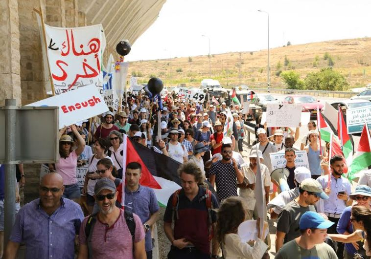Israelis and Palestinians marching next to the separation barrier on their way to the Tunnels Checkp