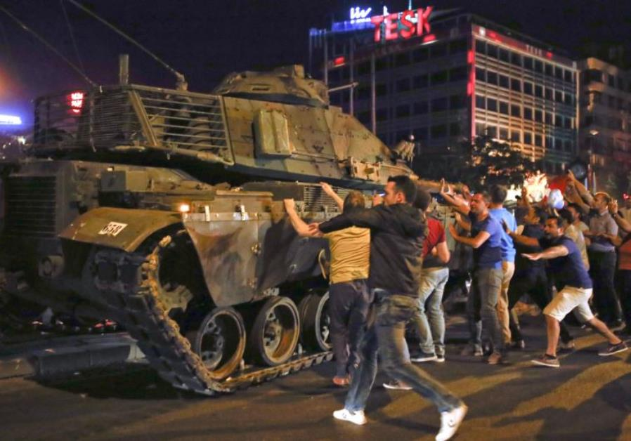 People react near a military vehicle during an attempted coup in Ankara, Turkey, July 16, 2016.