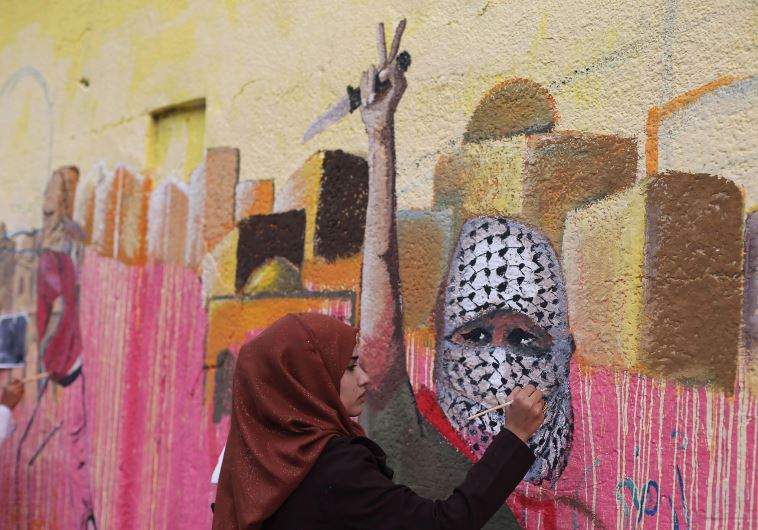 A PALESTINIAN woman paints a mural in support of Palestinians committing stabbing attacks against Is